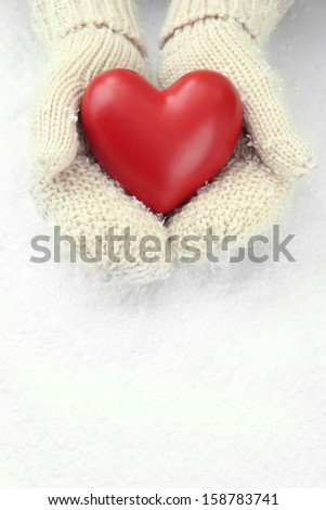 Female hands in mittens with red heart, close-up - stock photo