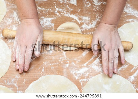 female hands is rolled piece of dough with rolling pin on kitchen table