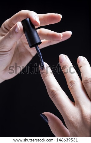 Female hands, isolated on black background, put the glaze to themselves - stock photo