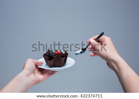 Female hands keeping cake with spoon on gray - stock photo