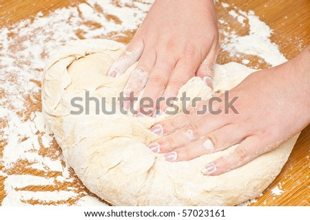 female hands kneading dough on table - stock photo