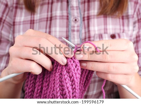 Female hands knitting with spokes close up