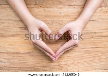 Female hands making an heart shape on wood - stock photo