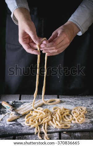 Female hands making pasta pici over wooden kitchen table, powdering by flour. Dark rustic style. - stock photo