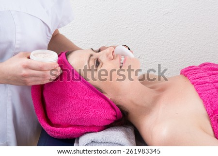 Female hands massaging young woman s face - stock photo