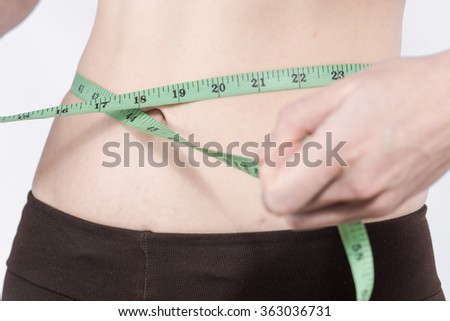 Female hands measuring the waist. The image of the part of female figure. Concept of fitness and body care.