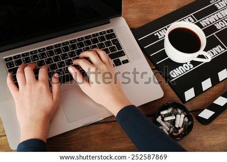 Female hands of scriptwriter working on laptop at wooden desk background - stock photo