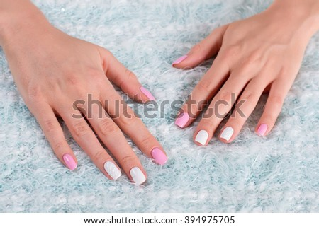 Female hands on a fluffy cloth. Beautiful white-pink manicure with ornaments.