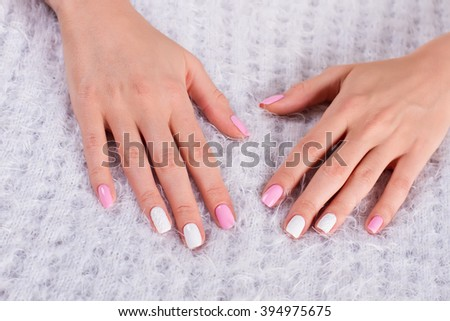 Female hands on a soft background. Delicate spring manicure.