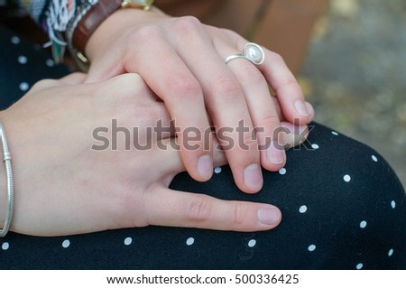 Female hands on knees in pants background autumn