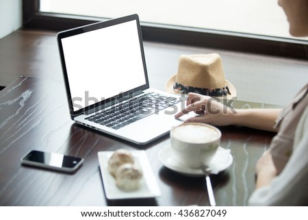 Female hands on laptop touch pad. Woman sitting with cup of coffee and cakes and working. Attractive model using computer with blank white copy space screen in cafe. Close-up - stock photo