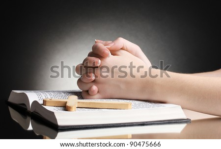 Female hands on open russian holy bible on black backround - stock photo
