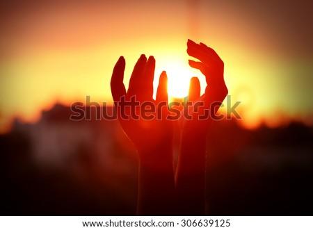 Female hands on sunset background - stock photo