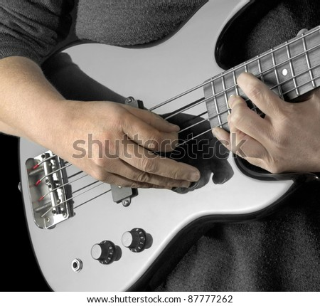 female hands on the detail of a black bass guitar in dark back - stock photo