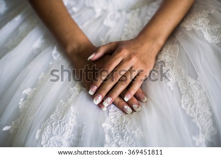 female hands on the wedding dress, the bride morning, preparing for the wedding, white nails, manicures - stock photo