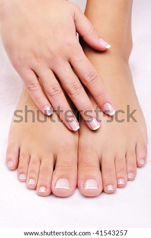 female hands on the well-groomed feet with french pedicure - stock photo