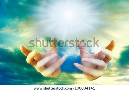 female hands over a beautiful sky with rays of light - stock photo