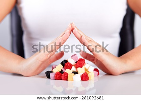 Female hands over a pyramid of candies - stock photo