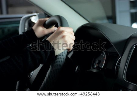 female hands over a wheel in the car - stock photo