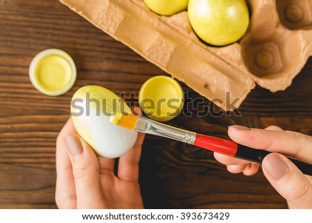 Female hands painted Easter eggs in yellow color with a brush - stock photo