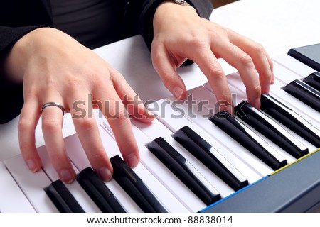 Female hands playing on keyboard - stock photo