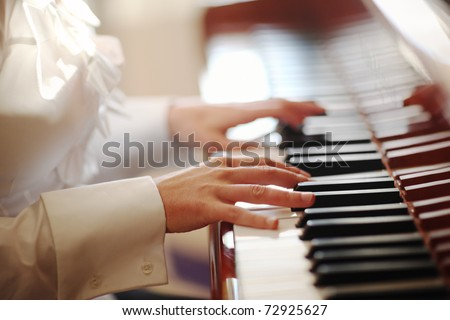 Female hands playing piano. Closeup, shallow DOF. - stock photo