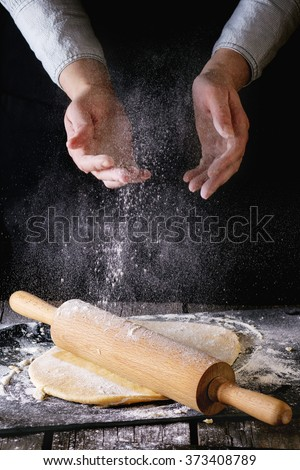Female hands powdered by flour rolled out dough for pasta with wooden rolling pin over wooden kitchen table. Dark rustic style. - stock photo