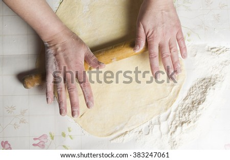 female hands rolling out dough with a rolling pin on a white table - stock photo
