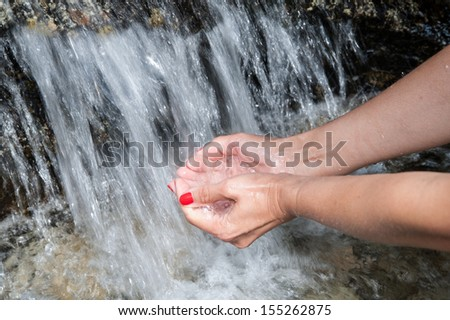 Female hands scoop up water in a fast river - stock photo