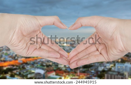 Female hands shaping a heart symbol with blur city background - stock photo