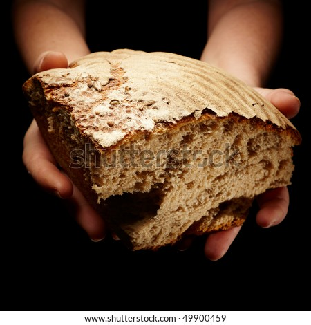 female hands sharing a sliced loaf of bread - stock photo