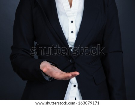 Female hands showing something on grey background