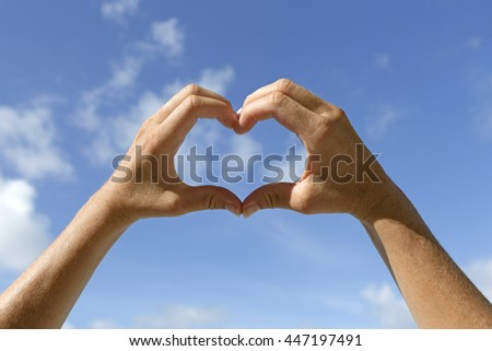 Female hands shows love sign in the air with blue sky