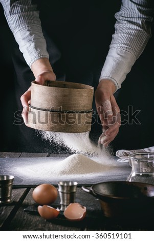 Female hands sifting flour from old sieve on old wooden kitchen table. Vintage kitchenware with flour, water and eggs at foreground. Dark rustic style with rertro filter effect. See process series - stock photo