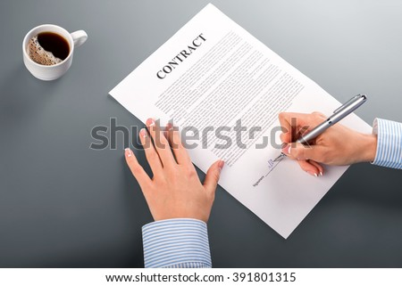 Female hands sign contract. Close-up of businesswoman signing contract. Morning coffee and paperwork. Finally a smart decision. - stock photo