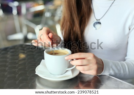 Female hands stirred the coffee in the cup - stock photo
