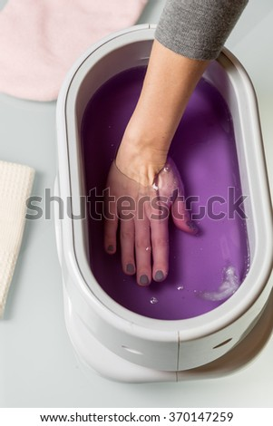 Female hands taking procedure in a lilac paraffin wax  bowl. Cosmetology and skincare equipment in a beauty & spa salon. - stock photo