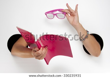 Female  hands through the holes on a white background are holding a pink book and glasses - stock photo