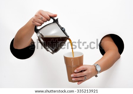Female  hands through the holes on a white background pour coffee from coffee pot into a cup - stock photo