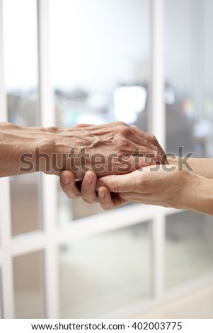 Female hands touching old male hand - taking care of the elderly concept - stock photo
