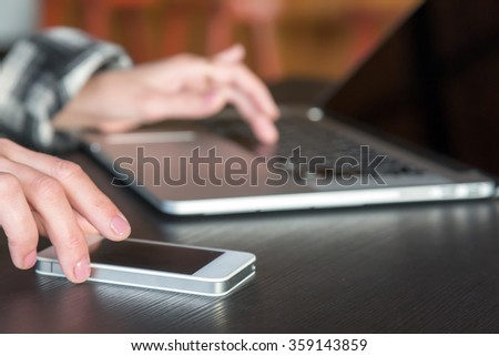 Female Hands touching Telephone Screen and working on Laptop Computer located on black Wood Desk with focus on Smart Phone front Edge - stock photo