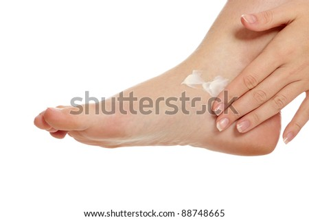 Female hands treating feet with moisturizing cream, isolated on white - stock photo