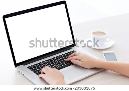 Female hands typing on a laptop keyboard with isolated screen in a white room on a desk with a phone and a cup of coffee - stock photo