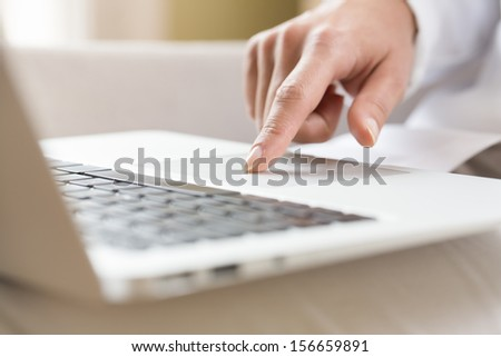 Female hands typing on a laptop trackpad - stock photo