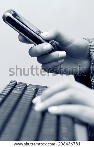 Female hands typing on computer keyboard and calling on cell phone  - stock photo