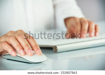 Female hands typing on keyboard and holding computer mouse on light background - stock photo
