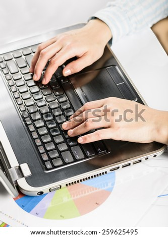Female hands typing on laptop. Closeup of woman hands using a laptop computer with financial statistics under it - stock photo