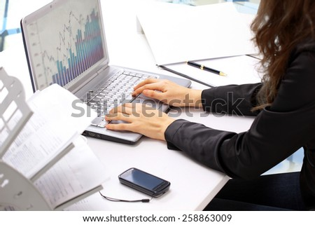 Female hands typing on the keyboard and while holding the mouse. Analysis of the graphs of sales.