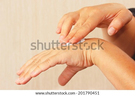 Female hands using a cosmetic skin cream - stock photo