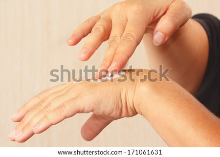 Female hands using a moisturizer for the skin close up - stock photo